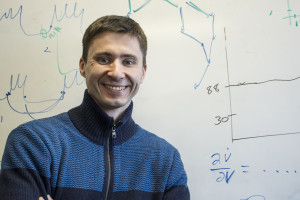 Associate Professor Igor Belykh, who is helping with solving problems the robotic fish project faces, poses in front of a board of his own equations. Photo by Jade Johnson | The Signal