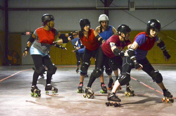 Barbara Tushbant (white helmet) blocks against four members of the opposing team during practice.