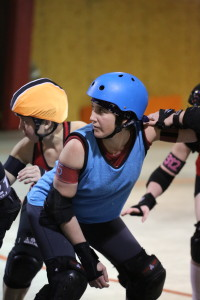 A jammer of the Atlanta Rollergirls is in position during a scrimmage game where they practice in a Norcross warehouse. Photo by Jason Luong   The Signal