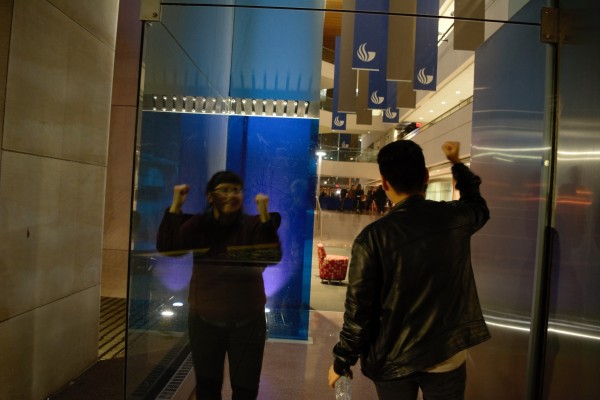 Protesters bang on the glass of the Honors College and chant rhythmically. Photo by Sean Keenan | The Signal