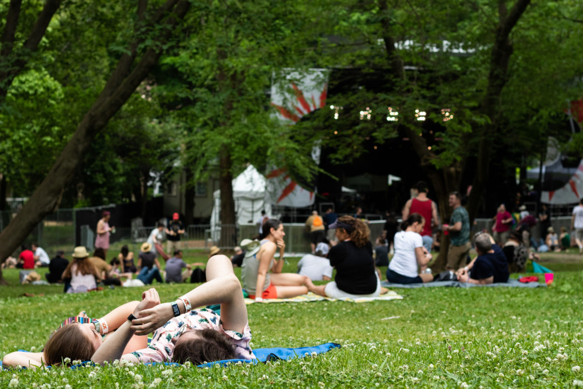 Friends relax in the grass in front of the Criminal Records stage between sets. Photo by Vanessa Johnson | The Signal