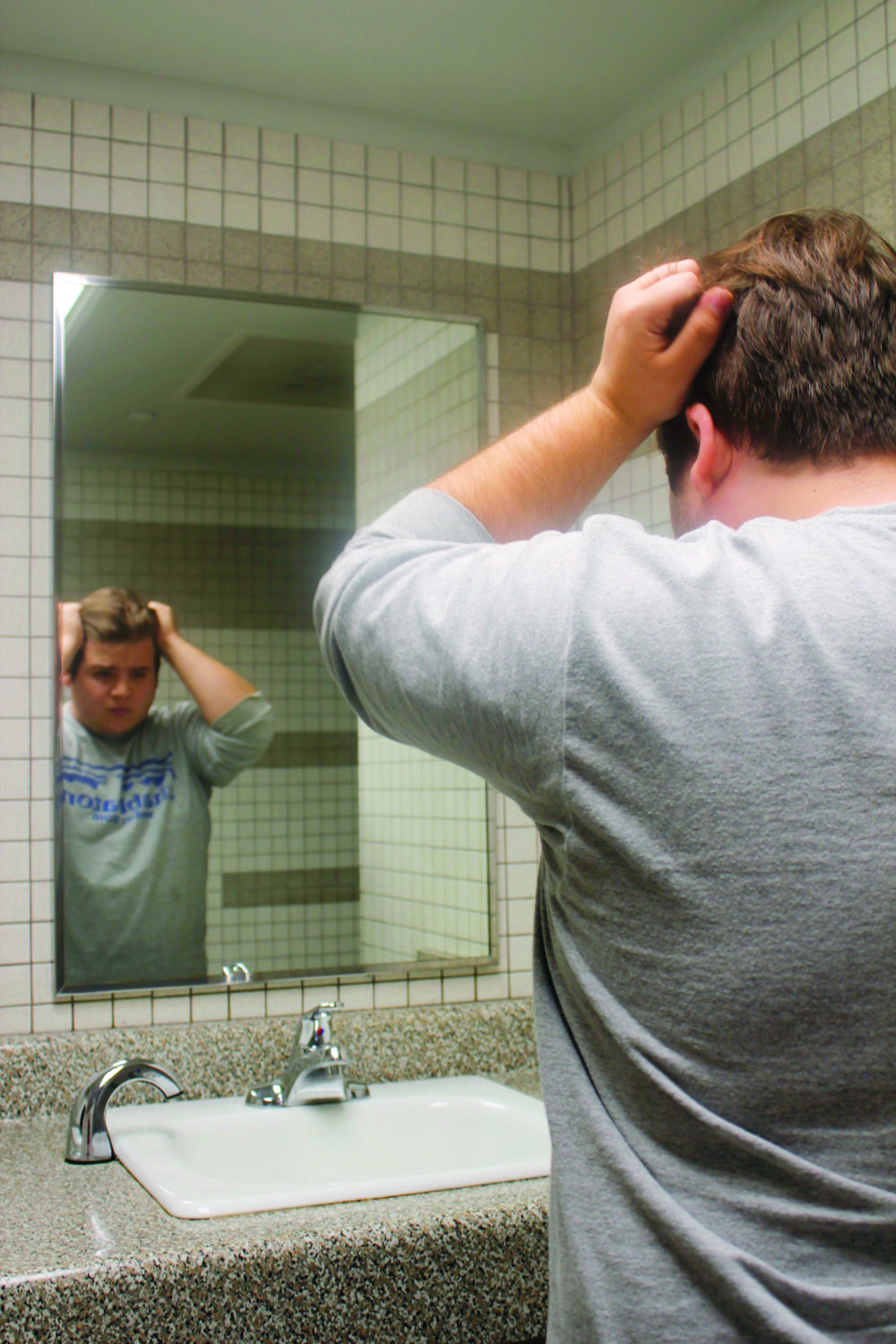 White male stands in front of a mirror