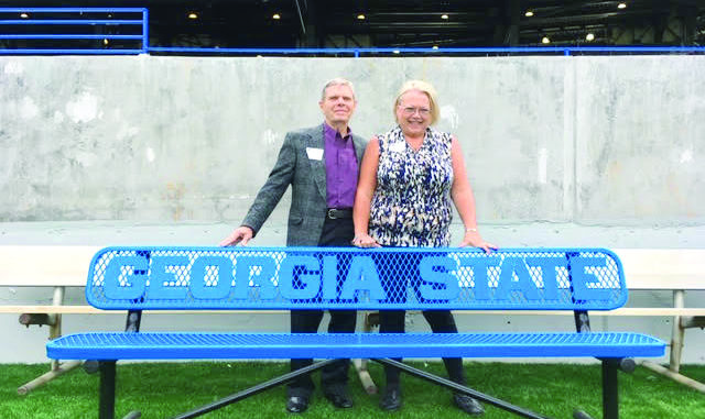 2 white people stand next to a bench at the Georgia State Stadium